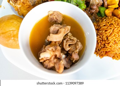 Top view of Nigerian goat meat pepper soup in small white soup bowl with bread bun and jollof rice for Nigerian party cuisine and food concept