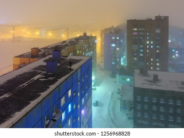 Top view of the night city. Snowfall and foggy mist on a cold winter late evening in the arctic. Colorful street lighting of a large northern city. Norilsk, Krasnoyarsk region, Siberia, Russia.