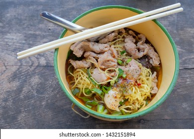 Top view thai​ noodle with pork meat and soup on wooden table