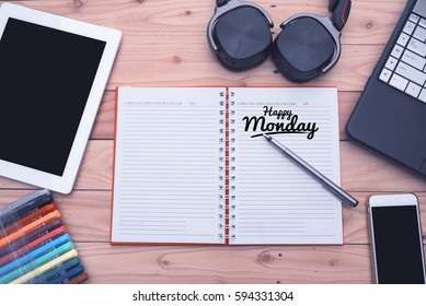 """Top view note book, communication device and gadget on wooden table with word """"Happy Monday""""."""