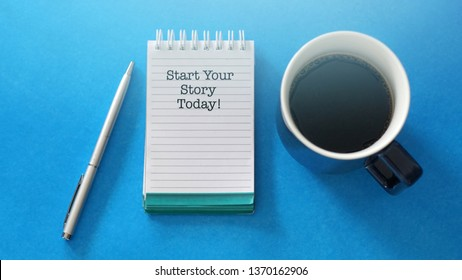 "Top view of a note book with a motivational phrase ""Start Your Story Today"" with coffee and a pen on blue background"
