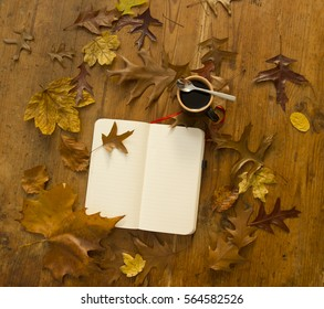 top view of a notebook, autumn leaves and coffee on wooden table