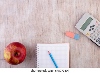 Top view of notebook with calculator pen and apple on wooden desk. Educational concept