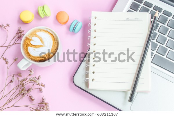 Top view of notebook with coffee and macarons on pink background,this image foe business concept.