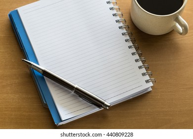 Top view of notebook with cup of coffee on wooden table