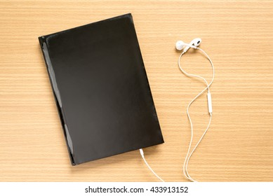 top view of notebook with earphone on wood background