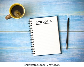 Top view of notebook handwriting goals for 2018 year, cup of coffee on blue wooden table. Business plan concept.