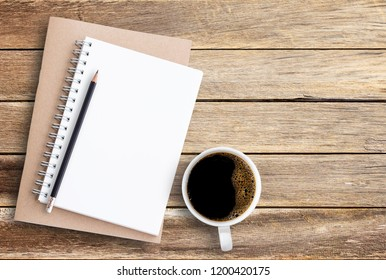 Top view of notebook pencil and cup of coffee on wood table background.Business desk minimal style concept with copy space for any design.