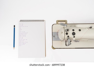 top view of notebook and pencil with sewing machine concept for designer business. flat lay style