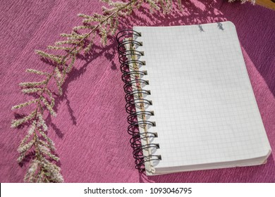 Top view of notebook with plastic spiral clasp holding squared papers. Sketchpad decorated with blossom and leaves branch isolated on purple background