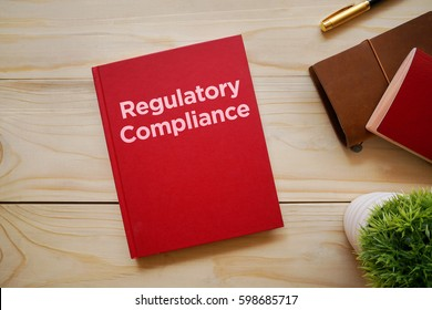 Top view of notebook with word Regulatory Compliance