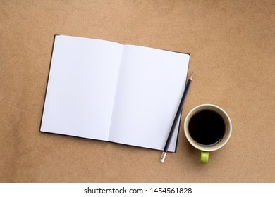 Top view of notebook,pencil and cup of coffee on wood table background.Business desk minimal style concept with copy space for any design.Take note of the product for book with paper.