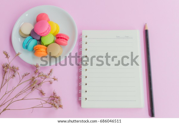 Top view of notebook,pencil,flower and macaron colourful on white dish and on pink background.