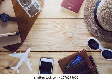 Top view of notebook,traveler accessories,camera,smartphone and airplane on wood table top background with copy space for text.Travel new year holiday vacation concept.