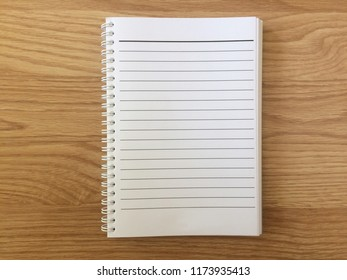 top view of notepad is blank form on wooden table. can be used montage for your graphic design wallpaper and free space for your text. business and education concept