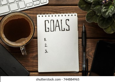 Top view of notepad with Goals List, cup of coffee on wooden table, goals concept, retro toned