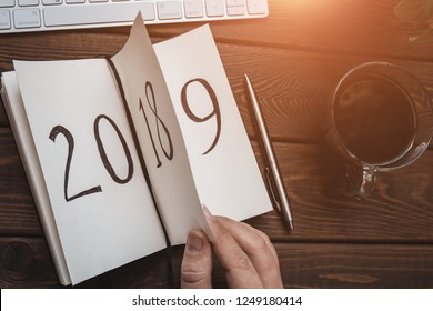 Top view of notepad on wooden table, female fingers flips sheet with 2018 and 2019 signs. Summing up last year concept, toned