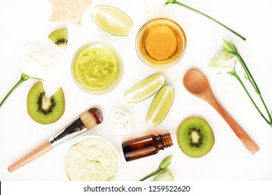 Top view nourishing natural skincare. Body balm & lime kiwi fruit slices, essential oils and face mask, bowl of honey, roses. Green ingredients white table background flat lay.