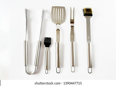 Top view object set of BBQ equipment stainless steel as tongs, carving fork, spatula. Isolated on a white background