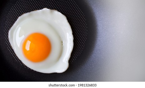 Top view of, Fried egg and Fresh yolk yellow uncooked in pan background with copy space, Preparation food or Breakfast with non stick kitchenware and oil free for Healthy food and Health care concept.