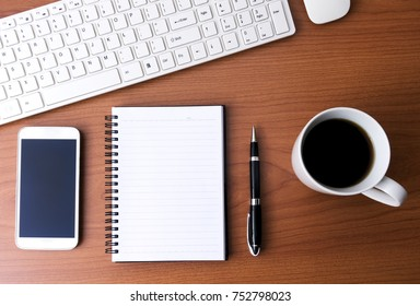 Top View Of Office Desk With Computer Keyboard, Smart Phone, Pen, Notepad, Mouse and Cup of Coffee on Wood Background.