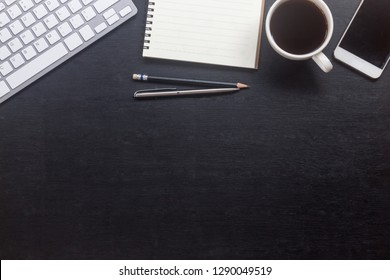 Top view of Office desk with hot coffee,notebook, keyboard and smartphone on top view and copy space. Flat lay of Business desk black table style concept. Work from home idea.