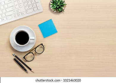 Top view of Office desk with keyboard, hot coffee, plant, vintage eyeglasses and color paper note on top view and copy space. Business desk minimal style concept with copy space.
