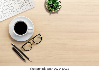 Top view of Office desk with keyboard, hot coffee, plant, vintage eyeglasses on top view and copy space. Business desk minimal style concept with copy space.