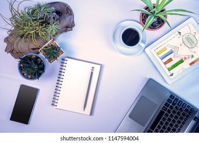 Top view of office desk with laptop, tablet, business goal sketch & flower vase