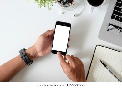 Top view office desk with mockup smartphone on hands with empty display screen.