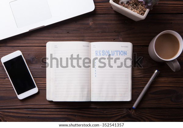 Top view office desk mockup: notebook, laptop, smartphone, snacks, and cup of coffee on rustic brown wooden background. New year resolution 2016