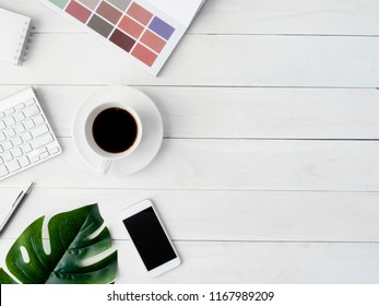 top view of office desk table with coffee cup, notebook, laptop, plastic plant, smartphone, pantone book and keyboard on white background with copy space, graphic designer, Creative Designer concept.