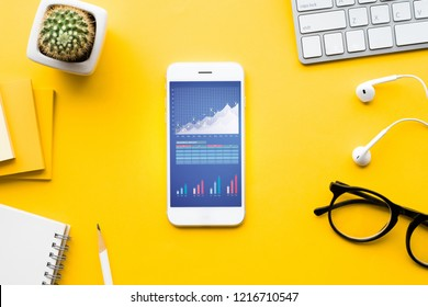 Top view of office desk table with graph chart on mock up smartphone,supplies on color background.flat lay design.business concepts ideas