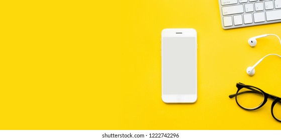 Top view of office desk table with mock up smartphone and modern accessories,supplies on color background.flat lay design.business concepts ideas