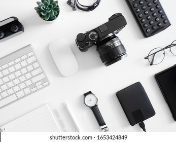 top view of office desk table with  calculator, notebook, plastic plant, smartphone and keyboard on white background, graphic designer, Creative Designer concept.