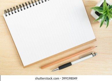 Top view of office desk table with open spiral notebook, pencil, and small tree in a white pot on wood table