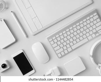 top view of office desk workspace with notebook, graphic tablet, smartphone and gadget on white background with copy space, graphic designer, Creative Designer concept.