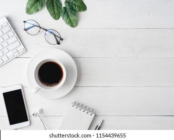 top view of office desk workspace with coffee cup, notebook, plastic plant, smartphone and keyboard on white background with copy space, graphic designer, Creative Designer concept.