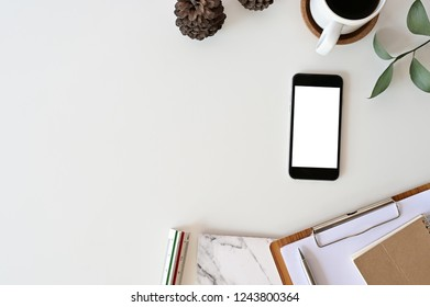 Top view office desk. Workspace with mockup smartphone, keyboard and office supplies, pencil, green leaf with coffee on white background.
