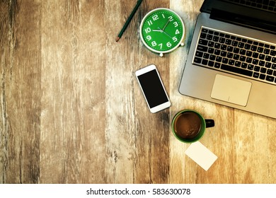 Top view of office desk and workspace as copy space with laptop computer, clock, cup of coffee, business card and smartphone