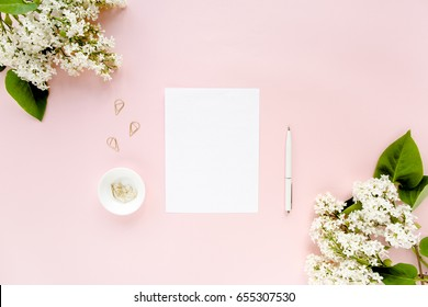 Top view office desk. Workspace with, computer, paper blank, bouquet lilac. Women's fashion accessories isolated on pink background. Flat composition for magazines, websites, media. Flat lay, top view