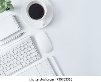 top view of office desk workspace with coffee cup, notebook, plastic plant, graphic tablet on white background with copy space, graphic designer, Creative Designer concept.
