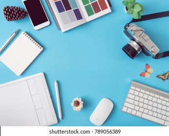top view office desk workspace with smartphone, notebook, graphic tablet, keyboard, pantone books and mouse on blue background with copy space, graphic designer, Creative Designer concept