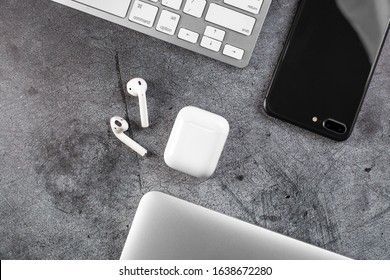 Top view Office desktop with office accessories, Desktop with business objects. metal background. Air Pods. EarPods. with Wireless Charging Case.