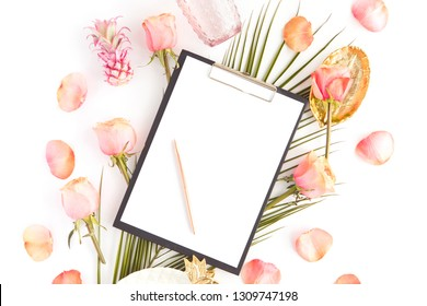 Top view of office female desk with blank screen tablet on tropical leaf, pink roses flowers on white background. Flat lay