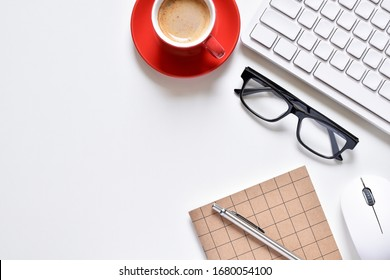 Top view office table, Creative design on table desk has book, pen, keyboard, mouse, eyeglasses and coffee cup with copy space.