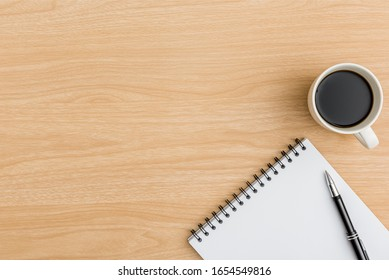 Top view office table desk. Flat lay Workspace with blank notebook, pen, coffee cup office supplies on wooden table background.