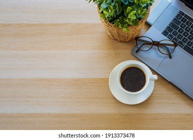 Top view office table desk. Workspace with blank, office supplies, laptop, eyes glasses, green leaf, and hot black coffee cup on wood background.