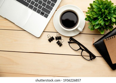 Top view office table desk. Workspace with blank, office supplies,Laptop, pencil, green leaf, and coffee cup on wood background.