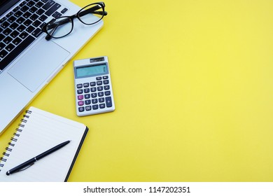 Top view office table desk.Table workspace with office accessories including laptop computer,notebook,pen,calculator,glasse on yellow background.Copy space for text.Blank empty page to word.Flat lay